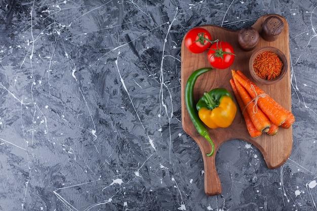 Pomidory, marchewki i różne papryki na drewnianej desce do krojenia.