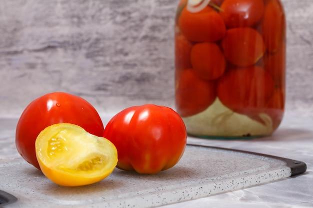 Pomidory marynowane w szklanym słoju na szarym tle.