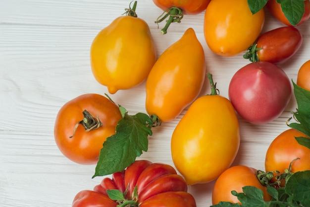 Pomidory na drewnianym stole. różne kolorowe pomidory na drewnianym stole. ekologiczne zielone, czerwone, żółte, pomarańczowe pomidory.