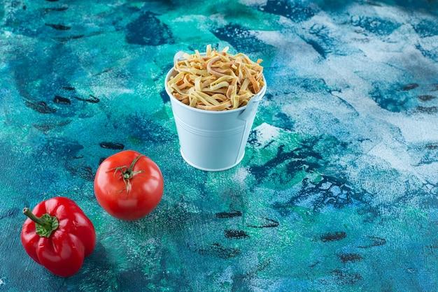 Pomidory, papryka i domowy makaron w wiadrze, na niebieskim stole.