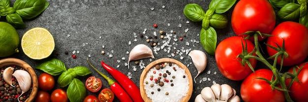 Pomidory, przyprawy i liście bazylii na czarnym tle