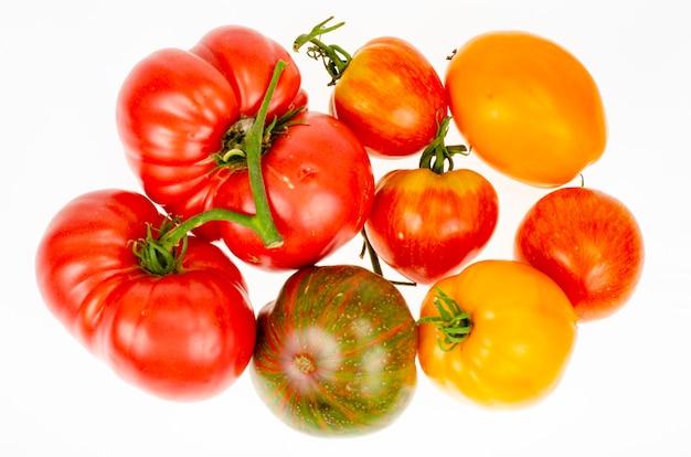 Pomidory różnych odmian i kolorów na białym tle, na białym tle. zbliżenie. martwa natura. mieszany. zdjęcie studyjne.