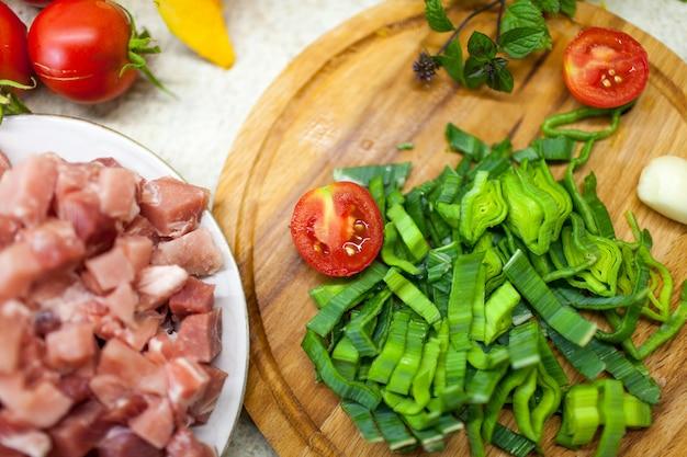 Pomidory są na planszy, obok warzyw i kawałków mięsa.