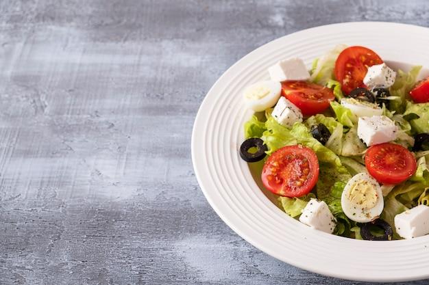 Pomidory sałatkowe ze świeżych warzyw, jajka przepiórcze, sałata, ser i czarne oliwki. koncepcja zdrowej diety i żywności.