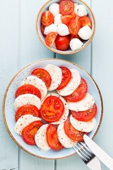 Pomidory, ser mozzarella, bazylia i przyprawy na szarej tablicy łupkowej. składniki sałatki włoskiej tradycyjnej caprese. jedzenie środziemnomorskie.