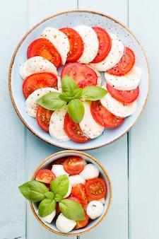 Pomidory, ser mozzarella, bazylia i przyprawy na szarej tablicy łupkowej. składniki sałatki włoskiej tradycyjnej caprese.