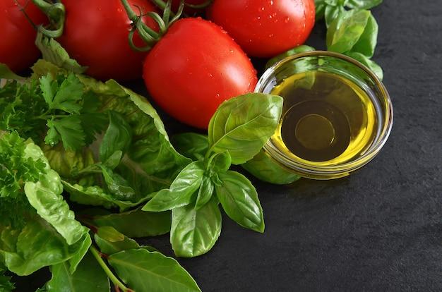 Pomidory, świeże liście bazylii i oliwy z oliwek na czarnym tle. zdrowe składniki żywności