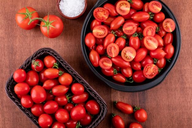 Pomidory w czarnej misce i w koszu pomidor czereśniowy i sól w ceramicznej misce na brązowej powierzchni kamienia