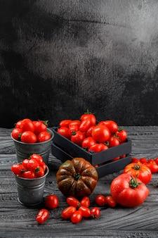 Pomidory w mini wiadrach, drewnianym pudełku na szarym drewnianym i grunge ścianie. wysoki kąt widzenia.