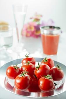 Pomidory w misce na białym stole (selektywne focus)