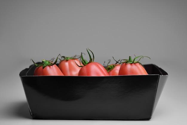 Pomidory w papierowym pojemniku świeże pomidory w pudełku na czarnym tle