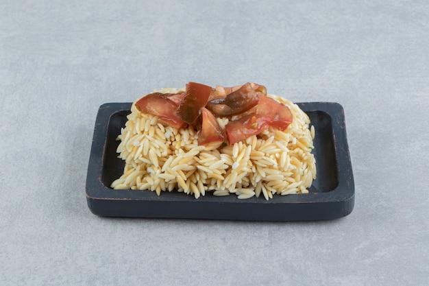 Pomidory w plastrach na drewnianym talerzu ryżowym, na marmurze.