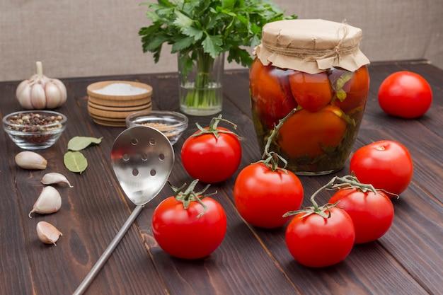 Pomidory w puszkach, czosnek i przyprawy. domowe produkty fermentacji. zdrowe odżywianie zimowe. czarna drewniana powierzchnia.