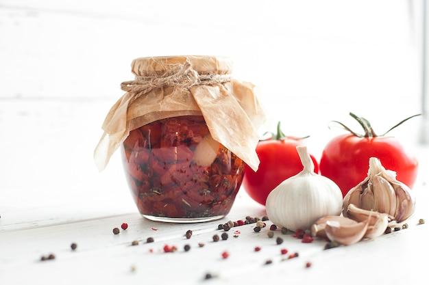 Pomidory w słoiku. domowe pomidory suszone na słońcu. tymczasowe zamknięcie. letnie i jesienne konserwy. konserwować z przyprawami i warzywami.
