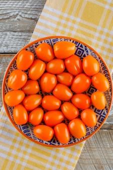 Pomidory w talerzu na ręczniku drewnianym i kuchennym. leżał płasko.