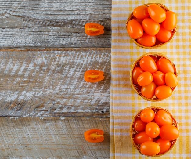 Pomidory w wiklinowych koszach na ręcznik drewniany i kuchenny. leżał płasko.