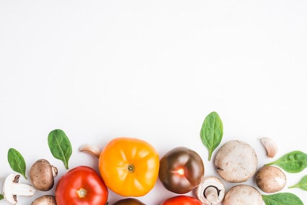 Pomidory wśród szpinaku i grzybów