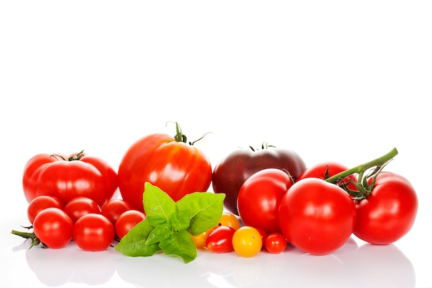Pomidory z bazylią na białym tle na białym tle w studio
