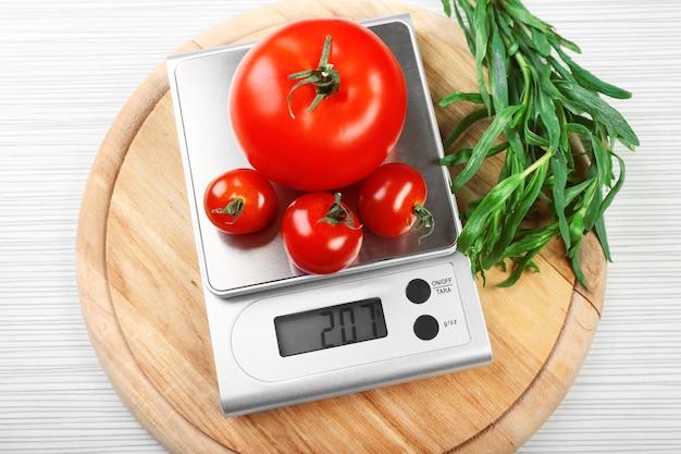 Pomidory z cyfrową wagą kuchenną na drewnianej ścianie