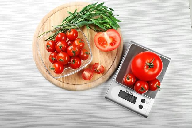 Pomidory z cyfrową wagą kuchenną na drewnianym stole
