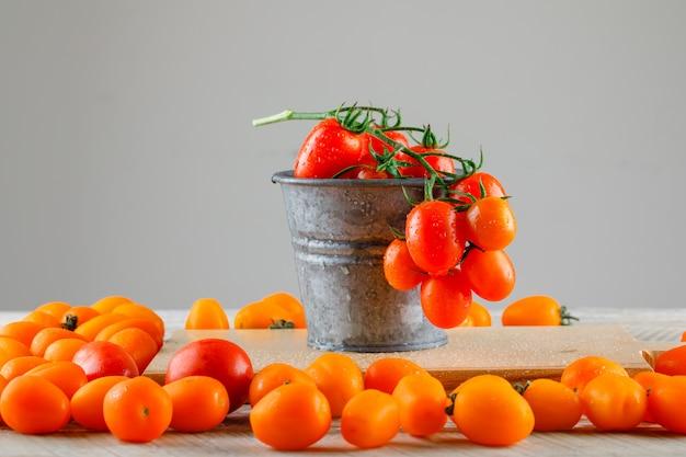 Pomidory z deską do krojenia w mini wiaderku na drewnianym stole, widok z boku.