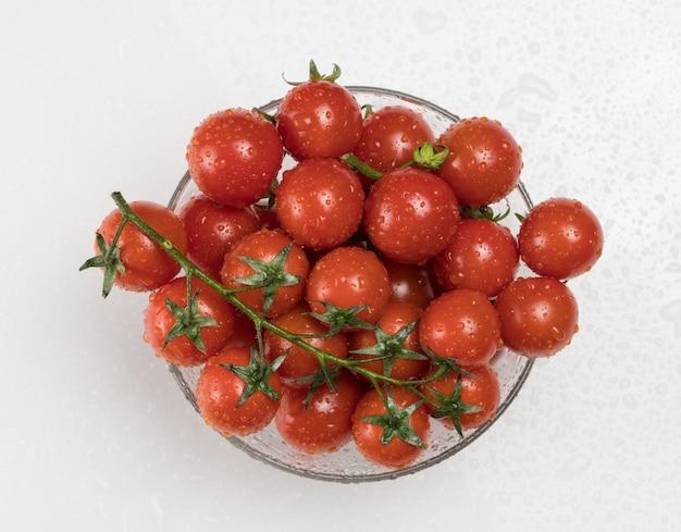 Pomidory z kroplami wody w szklanej misce na białym tle, widok z góry