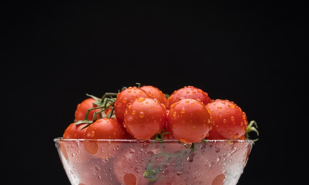 Pomidory z kroplami wody w szklanym naczyniu na czarnym tle, płaszczyzna pozioma