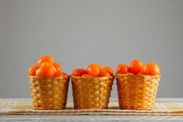 Pomidory z piknikową szmatką w wiklinowych koszach na drewnianym stole, widok z boku.