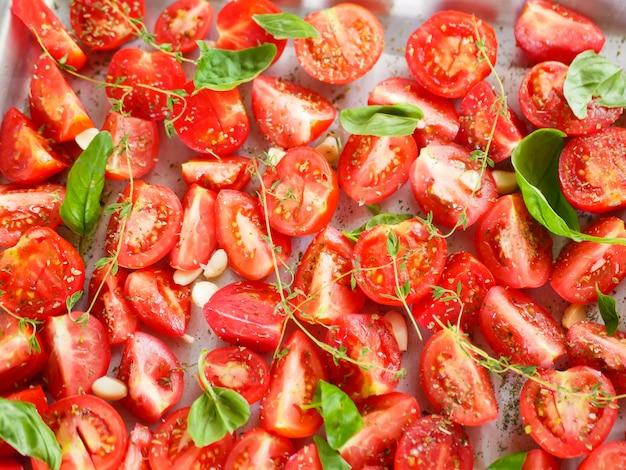 Pomidory z prowansalskimi ziołami, bazylią, tymiankiem i czosnkiem. wegetariański ratatouille z bakłażanów, cukinii, pomidorów i sosu z papryki i pomidorów z ziołami w formie ceramicznej przed pieczeniem. widok z góry.