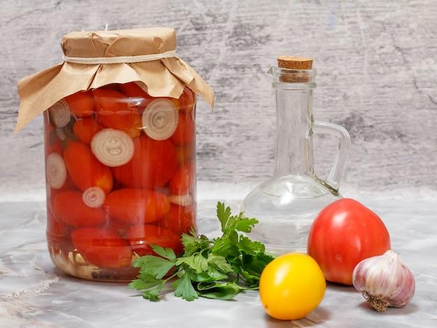 Pomidory zakonserwowane w szklanym słoiku, butelka octu i świeże pomidory, natka pietruszki, czosnek na kuchennym stole.