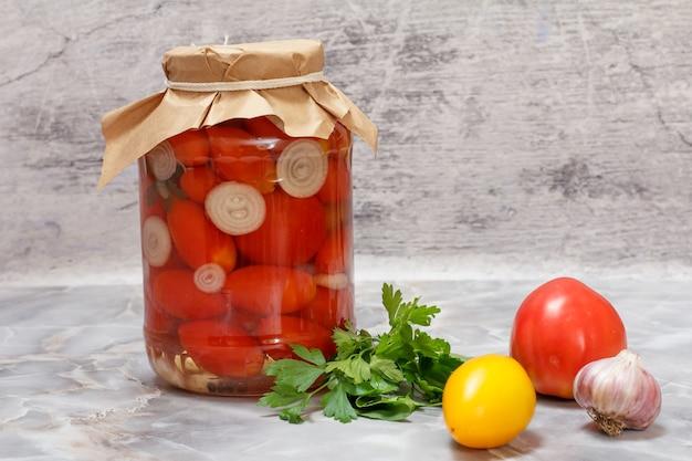 Pomidory zakonserwowane w szklanym słoju i świeże pomidory, natka pietruszki, czosnek na kuchennym stole.
