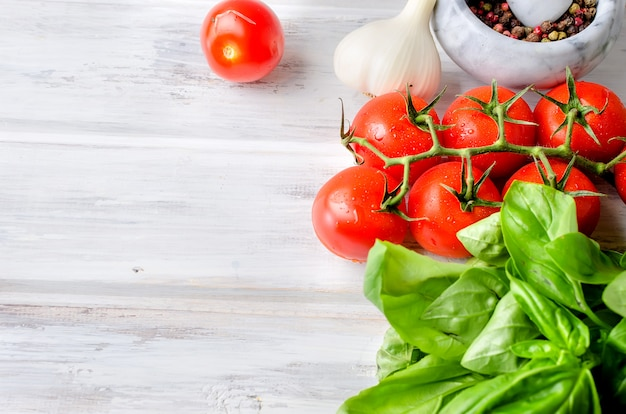 Pomidory, zielona bazylia i przyprawy w kamiennym moździerzu,