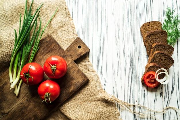 Pomidory, zielona cebula, koper, jaja przepiórcze, chleb, na białej tablicy