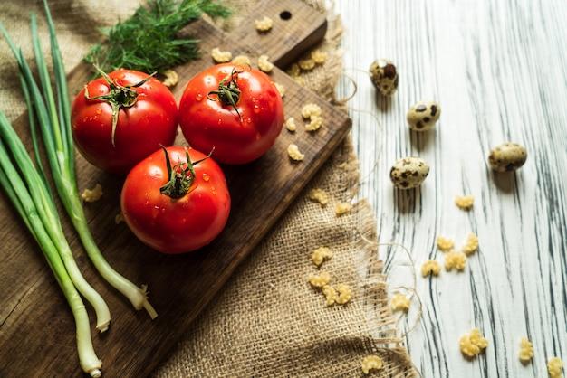 Pomidory, zielona cebula, koper, jaja przepiórcze na białej desce 2
