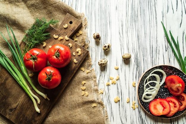 Pomidory, zielona cebula, koper, jaja przepiórcze na białej desce 3