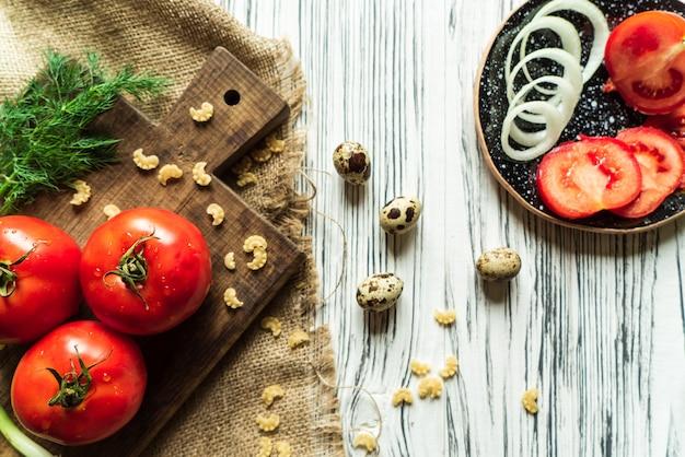 Pomidory, zielona cebula, koper, jaja przepiórcze na białej desce 4