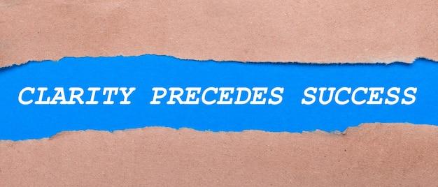 Pomiędzy brązowym papierem pasek niebieskiego papieru z napisem clarity precedes success. widok z góry