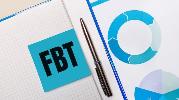 Pomiędzy niebieską karteczką z napisem fbt fringe benefit tax a niebieskim wykresem znajduje się długopis
