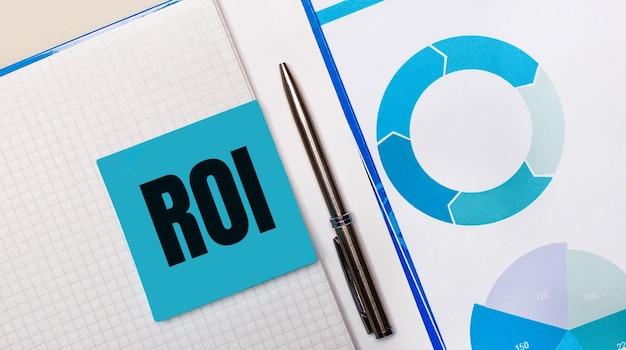 Pomiędzy niebieską karteczką z napisem zwrot z inwestycji roi znajduje się długopis
