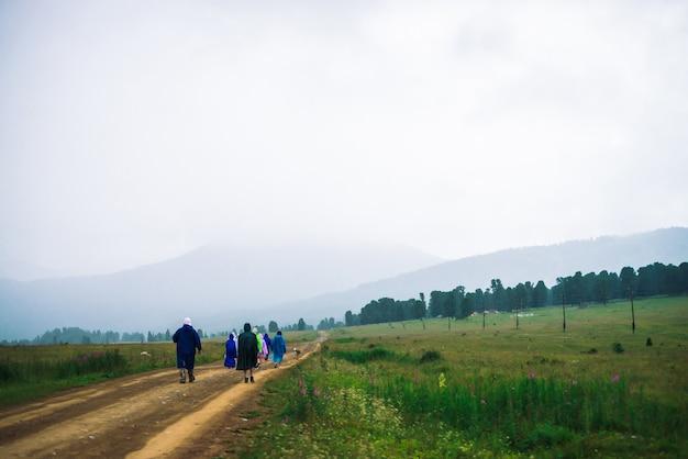 Pomimo złej pogody ludzie idą naprzód w górach. podróżni z psem idą w górę wzdłuż drogi. spacer po górach w deszczowy, pochmurny dzień.