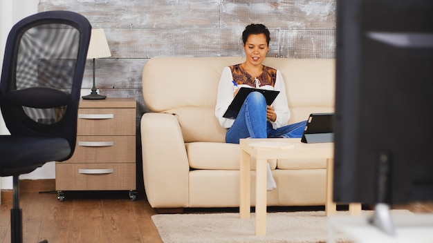 Pomniejsz strzał kobiety biznesu biorąc notatkę w schowku podczas rozmowy wideo na komputerze typu tablet pracujący w domu.