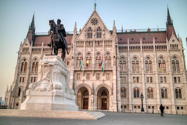 Pomnik andrassy gyula lovasszobra przed piękną historyczną fasadą węgierskiego budynku paliament na tle jasnego jesiennego nieba w budapeszcie na węgrzech.