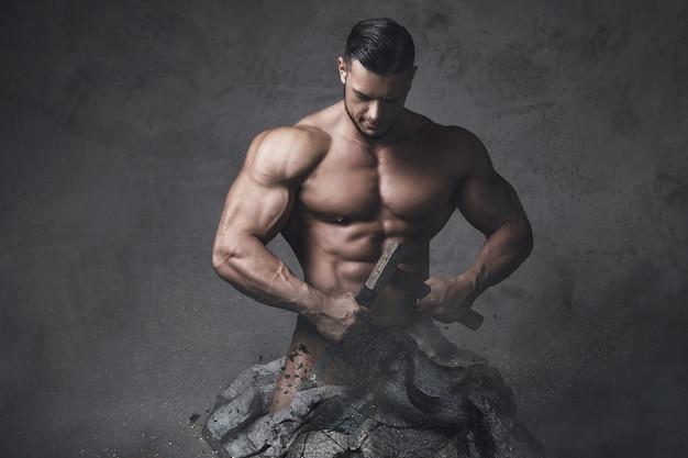 Pomnik muskularny mężczyzna. kulturysta wykonał się z kawałka kamienia. pojęcie samodoskonalenia i postępu w kulturystyce.