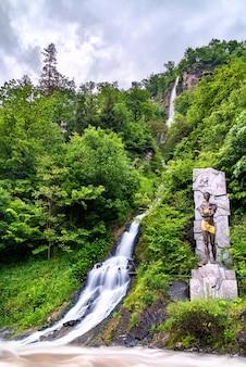 Pomnik prometeusza i wodospad w parku centralnym borjomi, gruzja