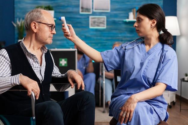 Pomoc asystenta pracownika pomiaru temperatury niepełnosprawnego starszego mężczyzny za pomocą medycznego termometru na podczerwień podczas terapii lekowej. opieka społeczna opiekująca się starszym mężczyzną na emeryturze. pomoc zdrowotna