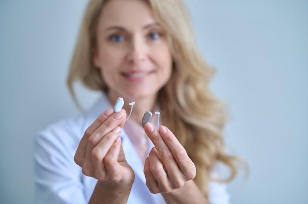Pomoc dla głuchoty. dwa różne aparaty słuchowe w wyciągniętych rękach uśmiechniętej ładnej kobiety w medycznej sukni na jasnym tle