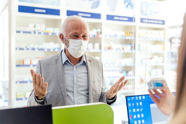 Pomoc farmaceutów. zdezorientowany starszy mężczyzna zasięga porady farmaceuty w sprawie terapii przepisanej przez lekarza. jest w eleganckim garniturze i ma na twarzy maskę ochronną