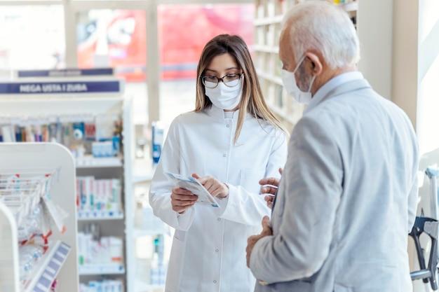 Pomoc farmaceuty. farmaceutka w okularach trzyma apteczki i instrukcje użytkowania. patrzy na mężczyznę, który wyjaśnia coś innego. oboje noszą maski ochronne