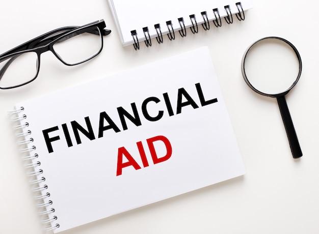 Pomoc finansowa jest zapisana w białym zeszycie na białym tle obok zeszytu, okularach w czarnych oprawkach i lupie.