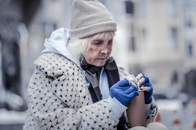 Pomoc finansowa. nieszczęśliwa biedna kobieta siedząca na ulicy, patrząc na posiadane pieniądze